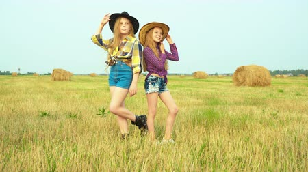 jeans short : Girls in cowboy hats standing on field in countryside. Adorable teenage girls in shorts and checkered shirts standing back to back and posing on beautiful autumn field with haysracks during harvest.