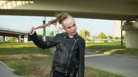 pozisyon : Girl Wear Black Jacket City Highway Background. Caucasian Female Teenager Play Long Ponytail Hair Leather Coat Clothes. Funny Kid Makeup Look Freckled Face Urban Motorway Road Pastime Concept Stok Video