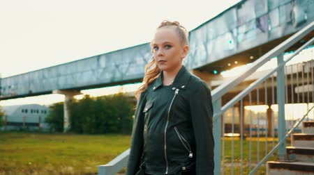 serseri : Teenager girl in black leather jacket walking on stairs on urban background. Young girl on sunflare background. Rock girl in city in sunshine backlit Stok Video