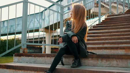 rockero : Teenager girl in black leather jacket sitting on stairs on urban landscape. Stylish girl in black leather jacket sitting on staircase looking away