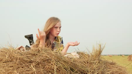 grimacing : Teenager Girl Lay on Haystack Beautiful Sunny Day. Caucasian Blond Hair Kid with Freckles Relaxing on Dry Hay at Harvesting. Happy Beauty Grimacing, making Heart with Hands. Rural Summer View Stock Footage