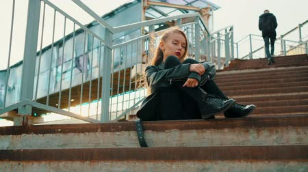 serseri : Teenage Girl in Leather Jacket Sitting on Stairs. Young Caucasian Fashion Model in Black Posing on Staircase. Beautiful Blond Teenager in Grunge Style Clothes on Urban Street Background Stok Video