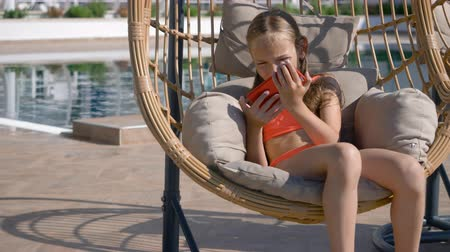 focalizada : Girl swinging in cocoon chair and using smartphone. Cute teenage girl in swimwear resting in cocoon chair near pool and using red cell phone