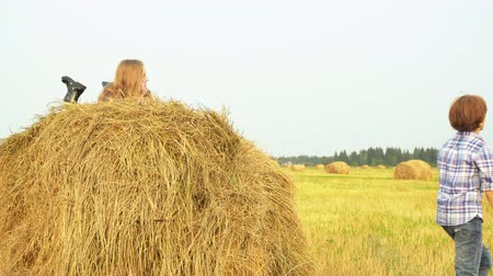 palheiro : Boy standing on field and girl lying on haystack. Cute teenage boy standing on autumn field during harvest and happy beautiful girl lying on haystack