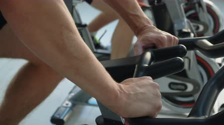 afslanken : Male hands on handle indoor bike in fitness studio. Man spinning bike on cycling class in gym. Fitness man training exercise on static bike in sport club