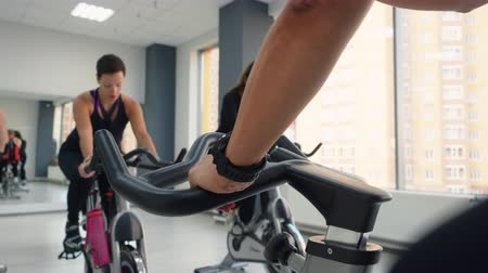 jimnastik : Sporty men and women cycling together in gym. Athletic people in sportswear cycling with coach on exercise bikes in gym Stok Video