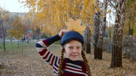 blue braid : Girl teenager in striped clothes and blue cap with yellow maple leaf near head like crow. Portrait happy girl with autumn foliage in autumn park. Beautiful model posing with autumn leaf in park