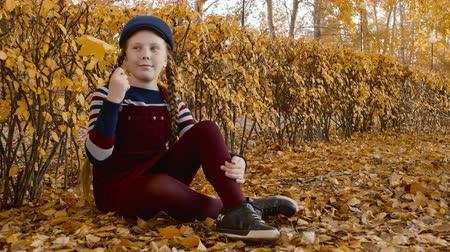 pet : Teenager girl in cap sitting on yellow leaves in autumn park. Beautiful girl holding maple leaf near face in orange city park at autumn day