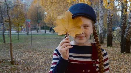 braid hair : Happy teenager girl holding yellow maple leaf in hand near face. Portrait playful girl with autumn foliage park. Face red haired girl with freckles posing for camera
