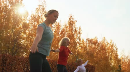 aerobic : Sport woman training choreography on outdoor class in autumn park. Female dancer group training dancing exercise in city park. Fitness woman practicing port de bras