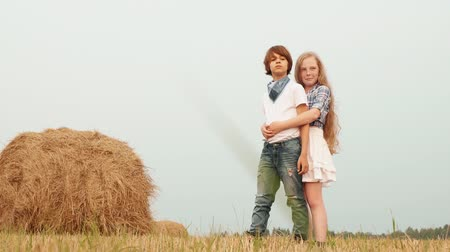 hooiberg : Teenager couple embracing on countryside field on haystack background. Young couple teenager girl and boy hugging on harvesting field in village Stockvideo