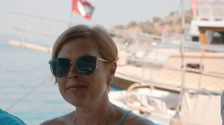 személyszállító hajó : Portrait adult woman with short hair and sunglasses on ship at sea walk. Face beautiful red haired woman sitting on sea boat and smiling to camera Stock mozgókép