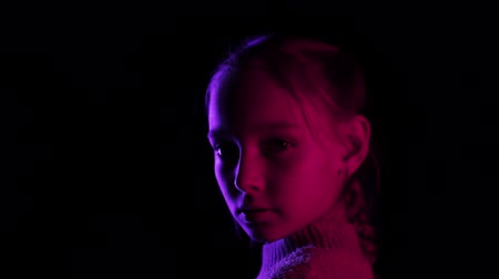 シック : Teenager girl turning around on black background in neon lighting. Portrait young girl looking to camera in dark studio in blue and red lighting 動画素材