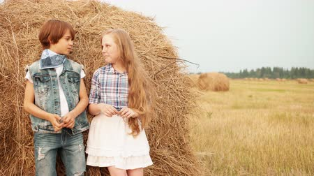 szalma : Romantic couple leaning back on haystack on harvesting field in countryside. Teenager girl and boy standing on haystack background on farming field in village