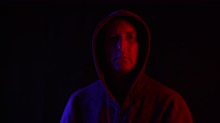 invisible : Man in dark hoodie looking up to camera on black background in blue and red lighting. Portrait mysterious man in hood in dark studio with red and blue backlight Stock Footage