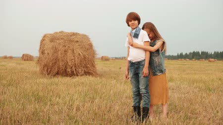 bağ : Young couple hugging on harvesting field on haystack background. Embracing teenager girl and boy posing on countryside field on haystack background in village