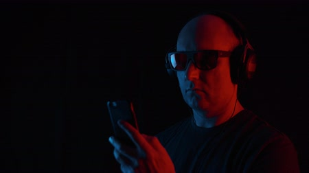 low lighting : Adult man listening mobile music in headphones on black background with red and blue lighting. Portrait bald man using smartphone and earphones for listening music on dark background