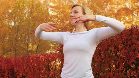 focalizada : Beautiful smiling young woman dancing and looking away in park. Attractive flexible woman in sportswear training and dancing in autumn park