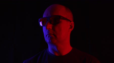 предназначенный только для мужчин : Bald man in dark glasses on black background in blue and red light. Portrait adult man in sunglasses in dark studio looking to camera, blue and red neon light on background