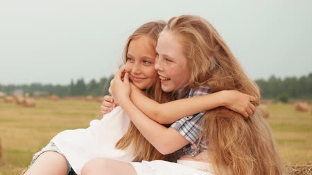 bales : Playful girls hugging on haystack on harvesting field at village vacation. Smiling girl friends embracing on haystack background on countryside field Stock Footage