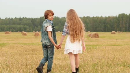 szénaboglya : Teenager couple holding hands walking on rural field on haystack background. Romantic girl and boy turning on harvesting field. Young couple posing in countryside field