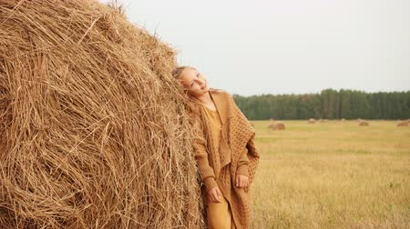 hayloft : Fashion girl posing on haystack background on harvesting field in countryside. Young teenager girl leaning on dry haystack on rural field in village