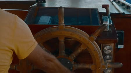 ステアリング : Cropped shot of captain helming ship with steering wheel. Close-up partial view of male hand on wooden steering wheel on ship