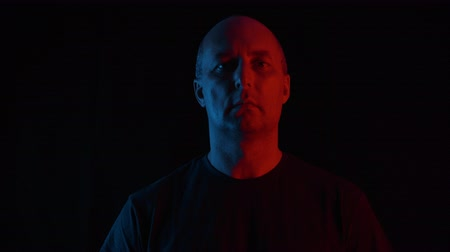 cabeza calva : Portrait of serious middle aged man looking at camera in darkness. Handsome confident bald mature man looking down and looking at camera on black background