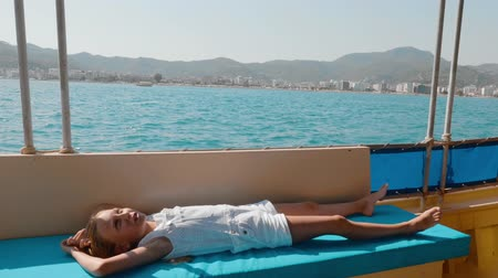 солнечные ванны : Tourist girl relaxing on floating yacht at sea walk. Young girl lying on sailing boat at summer cruise on sea. Teenager girl traveling in sea ship Стоковые видеозаписи