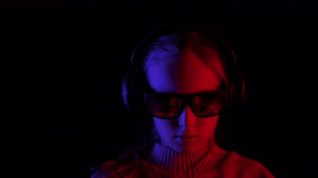 devise : Smiling girl listening mobile music in headphones and black sunglasses in dark studio with red and blue backlight. Teenager girl browsing music in earphones on black background