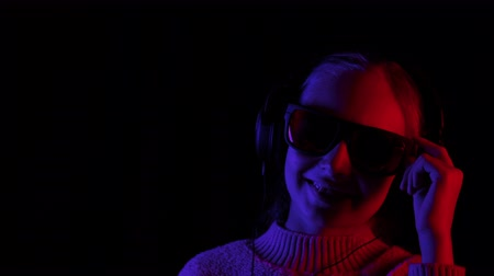 devise : Happy girl listening music in headphones and black sunglasses in dark studio with red and blue lighting. Teenager girl enjoying music in earphones on black background