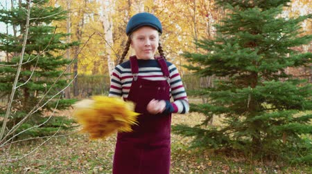 golden falls : Funny girl dancing with bouquet from autumn leaves in city park. Teenager girl dancing in autumn park. Cheerful girl having fun on autumn vacation Stock Footage