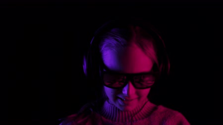 gadżet : Happy girl listening mobile music in headphones in dark studio with red and blue backlight. Teenager girl in black sunglasses listening music in earphones on black background