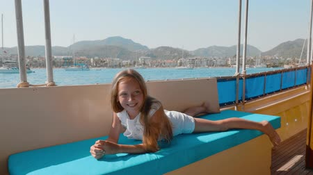 deitado : Carefree girl relaxing on couch sailing boat on sea cruise on mountain landscape. Tourist girl lying on ship couch in sea walk at summer trip Stock Footage