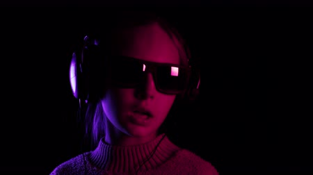 devise : Teenager girl singing and dancing in headphones in dark studio with red and blue lighting. Young girl listening music and singing song on black background