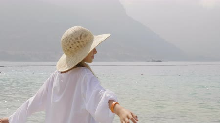 sombrero de paja : Young girl in straw hat on sea and mountain background in misty haze. Happy girl teenager posing on sea beach on green tropical island landscape Archivo de Video