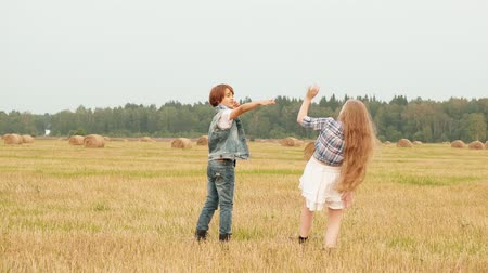 palheiro : Teenager girl and boy walking on harvesting field on haystack background. Happy girl and boy having fun on countryside field in village. Funny teen couple walking on autumn meadow
