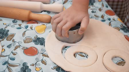 enrolado : Children hands cutting round pieces from rolled dough for baking cookies in culinary school. Young cook preparing dough for pastry in bakery master class. Cooking lesson in school
