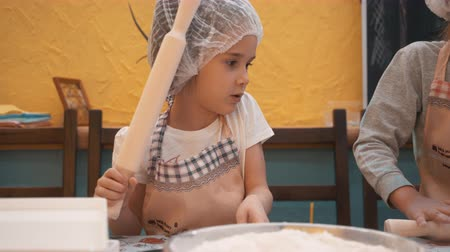 piekarz : Little girl in disposable cap preparing dough on school kitchen. Girl chef cook rolling thin dough with roller on cooking master class in culinary school. Cooking class kids in preschool