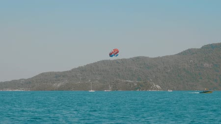 bezmotorové létání : Boats on sea waves and person parasailing above water. Scenic view of beautiful sea harbour with vessels and person gliding through air wearing open parachute above motorboat