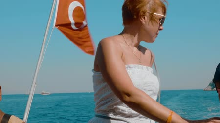 yüzer : Tourists sitting in boat and enjoying sea tip. Beautiful woman in sunglasses resting in motorboat with turkish flag floating on sea waves at summertime