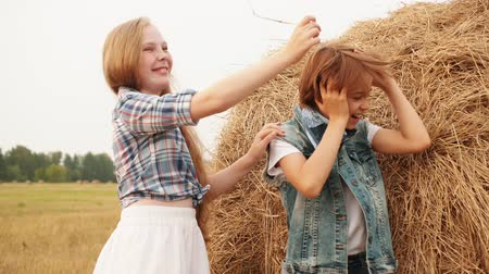 palheiro : Cute happy boy and girl playing with hay in field. Adorable cheerful teenage girl and boy having fun near haystack in rural area