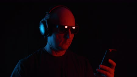 orange t shirt : Man in headphones in sunglasses using smartphone red orange and blue light in darkness. Portrait of handsome serious middle aged man in dark t-shirt, sunglasses and headphones using mobile phone