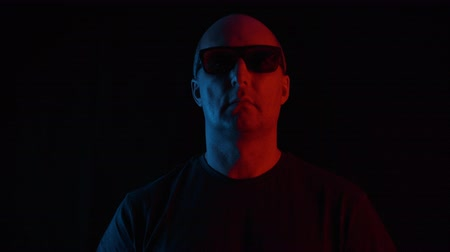 łysy : Serious middle aged man in sunglasses standing in darkness. Portrait of mature bald man in dark t-shirt and sunglasses standing and looking at camera on black background