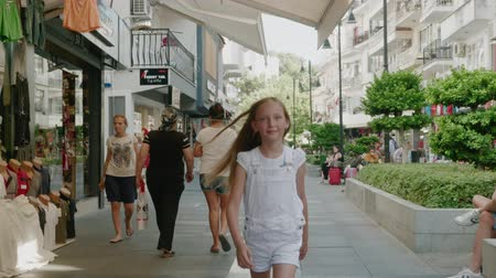istanboel : Antalya, Turkey - October 30, 2019: happy girl walking on shopping street in tourist city at vacation. Smiling girl teenager walking front camera on city street on shopping mall background Stockvideo
