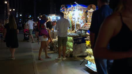 istanboel : Antalya, Turkey - October 30, 2019: tourist people walking on evening shopping street. People choosing souvenirs on shopping market in resort city at evening walk