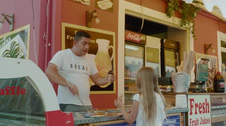 türkisch : Antalya, Turkey - October 30, 2019: young girl buying turkish ice cream from funny seller. Turkish ice cream man playing with girl buyer in outdoor street cafe