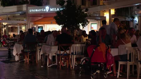 plezant : Bodrum, Turkey - October 30, 2019: people dining in outdoor evening cafe. Tourist people in outdoor restaurant on city street at evening dinner