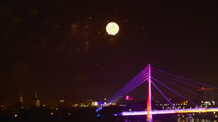 pirotecnia : Fireworks in night sky above urban city. Festive fireworks above bridge and illuminated buildings in dark sky at night time Vídeos