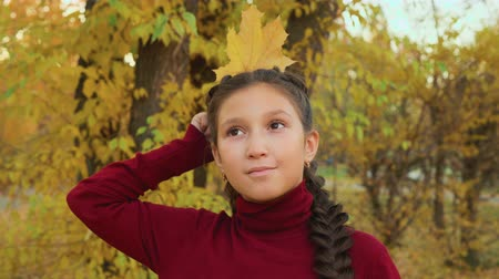 prenses : Brunette girl with braids holding maple leaf behind head like queen in autumn park. Portrait girl teenager with yellow leaf like crown over head in autumn park Stok Video